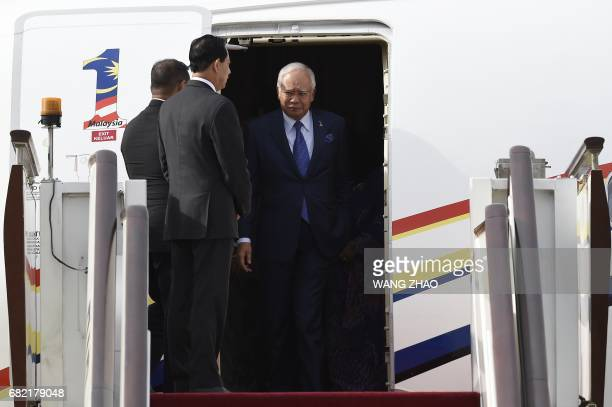 Malaysian Prime Minister Najib Razak walks out from the airplane upon his arrival at Beijing Capital International Airport on May 12,2017. Najib...