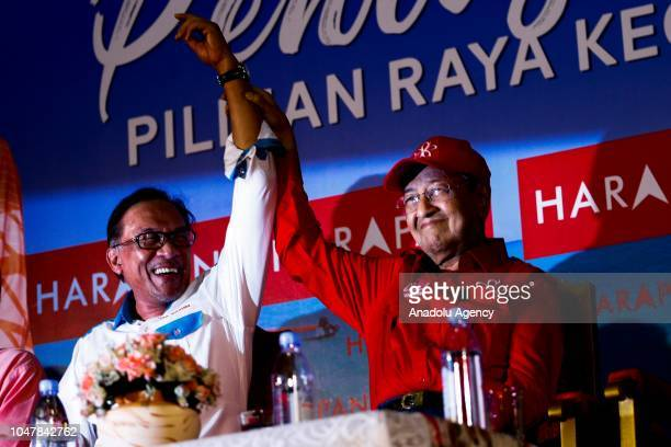 Malaysian Prime Minister Tun Mahathir Mohamad raises up Anwar Ibrahim's hand during byelection campaign in Port Dickson Malaysia on October 8 2018...