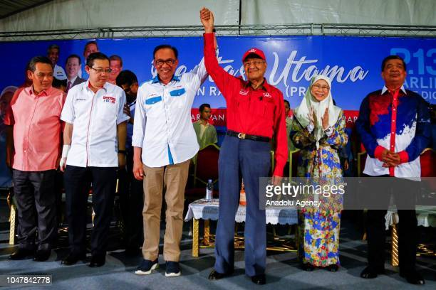 Malaysian Prime Minister Tun Mahathir Mohamad raises up Anwar Ibrahim's hand during byelection campaign at Port Dickson Malaysia on October 8 2018...