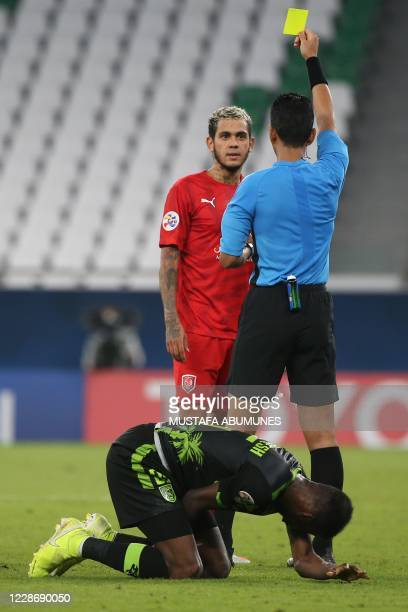 Malaysian referee Mohd Amirul Izwan presents a yellow card to Duhail's forward Edmilson Silva during the AFC Champions League group C match between...