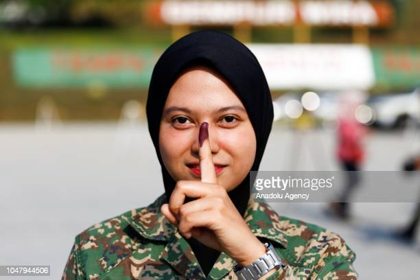 Malaysian Royal Army officer shows her inked finger during early voting ahead of the Port Dickson Parliament byelection at Army Basic Training Centre...