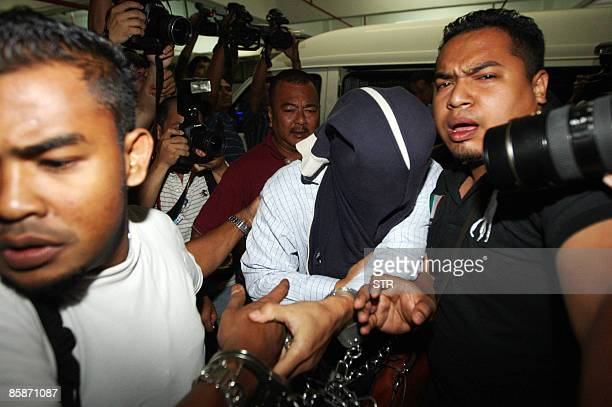 Malaysian security officers carry away one of the policemen with covered face found guilty in a Mongolian model girl murder case at Shah Alam high...