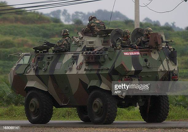 Malaysian soldiers with in an armored personnel carrier drive towards the area where the standoff with Sulu gunmen is on going in Tanduo village on...