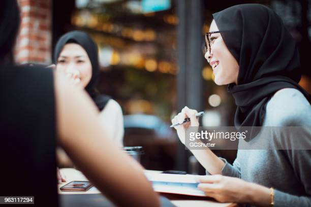 malaysian students having banter at a cafe - malaysian culture stock pictures, royalty-free photos & images