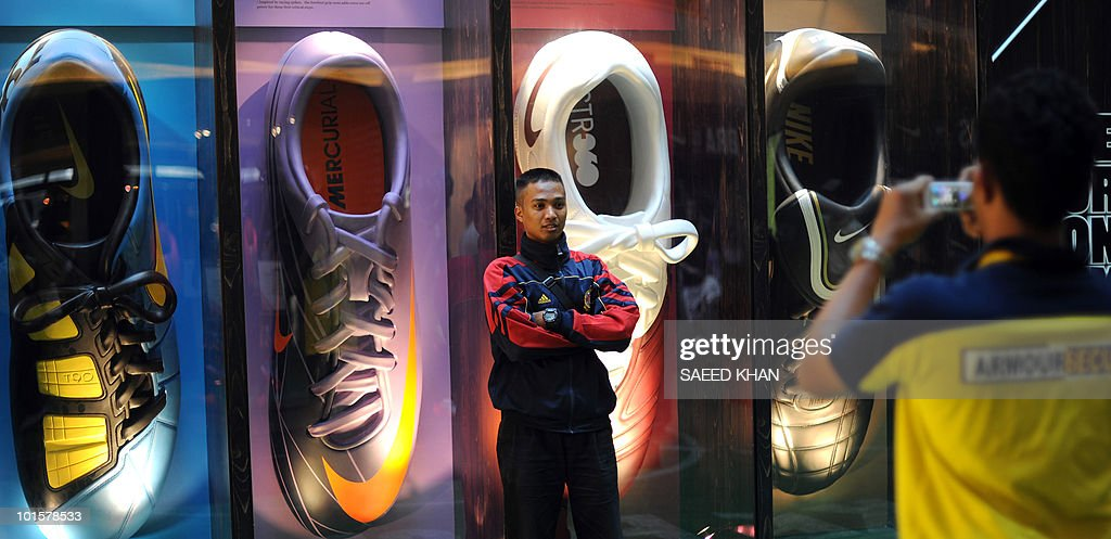 Malaysian students pose next to the models of Nike sports shoes for a 2010 World Cup promotion at a stall in Kuala Lumpur on June 3, 2010. Competition at the 2010 World Cup will not only be fierce on the football pitch but also at the sportswear shops, as historic brand leader Adidas faces off against rival Nike and a third challenger Puma. The football championships kick off June 11 in South Africa as Adidas hopes to retain its claim to the title of the number one football brand against a stiff challenge from the world's biggest sportswear manufacturer Nike. AFP PHOTO/Saeed KHAN