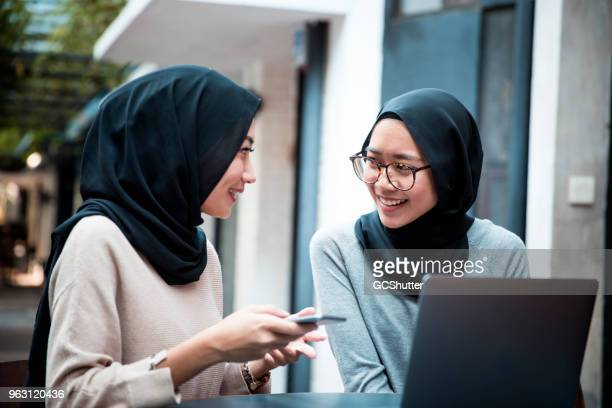 malaysian students wearing hijab at a cafe with their laptop and mobile phone - malay hijab stock photos and pictures