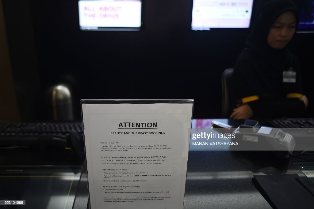A Malaysian ticket-seller sits behind a notice displayed regarding the release of the film 'Beauty and the Beast' at a Golden Screen Cinemas theatre in Kuala Lumpur on March 14, 2017