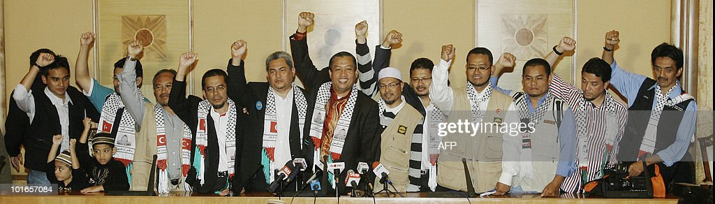 Malaysian volunteers who were onboard a humanitarian aid ship attacked by Israeli commandos on its way to Gaza, pose at Kuala Lumpur International Airport in Sepang on 6 June, 2010. Twelve Malaysian volunteers onboard the aid ship returned home.