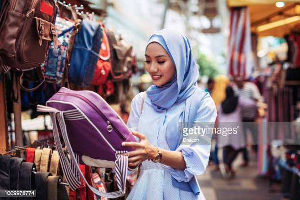 malaysian woman choosing fabrics at market - malay hijab stock photos and pictures