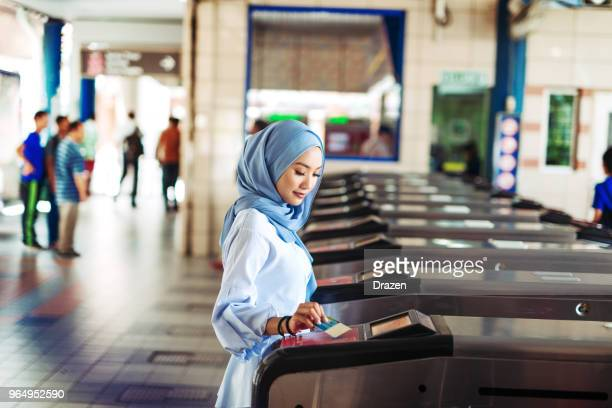 Malaysian woman entering train station platform