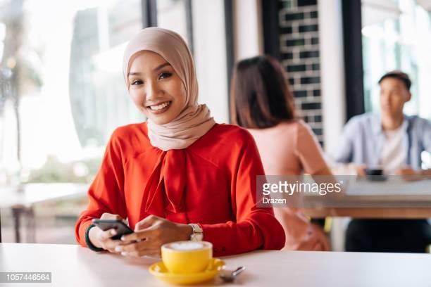 コーヒーを飲むと、携帯電話を見て、カフェでは、マレー人の女性 - ヘッドスカーフ ストックフォトと画像