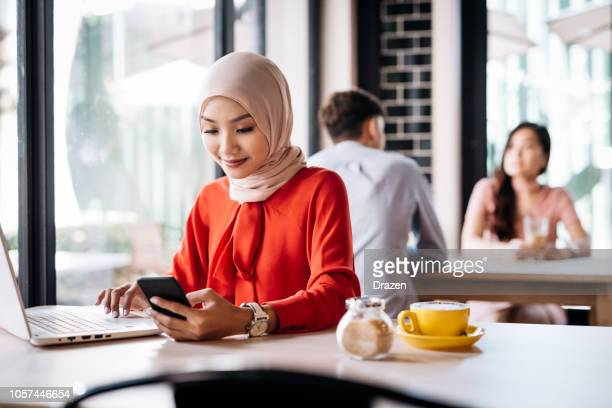 malaysian woman in cafe using electronic banking on laptop - islam stock pictures, royalty-free photos & images