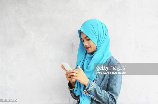 malaysian woman in hijab with smart phone - malaysische kultur stock-fotos und bilder