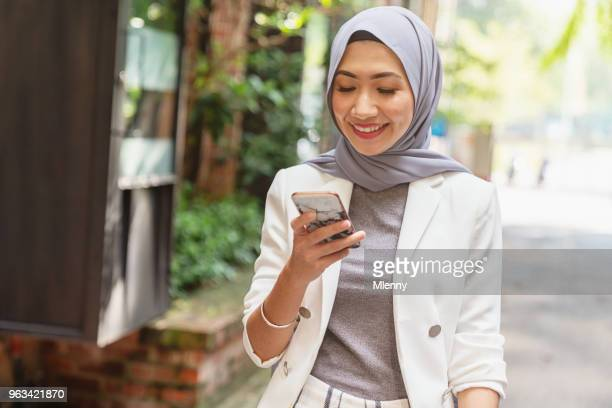 Malaysian woman reading messages on smart phone