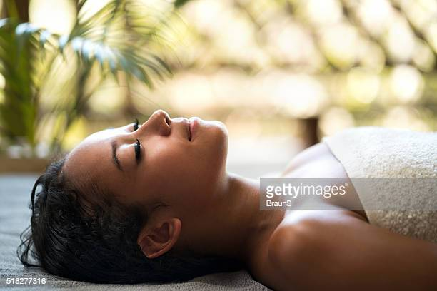 Malaysian woman relaxing at the spa with her eyes closed.
