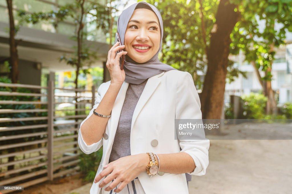 Malaysian woman walking in kuala lumpur talking on mobile phone : Stock Photo
