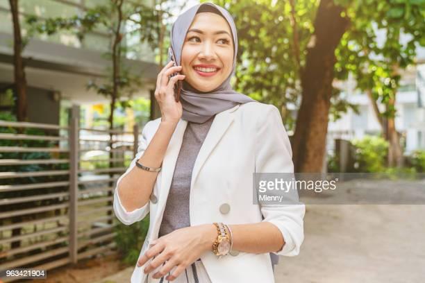 Malaysian woman walking in kuala lumpur talking on mobile phone