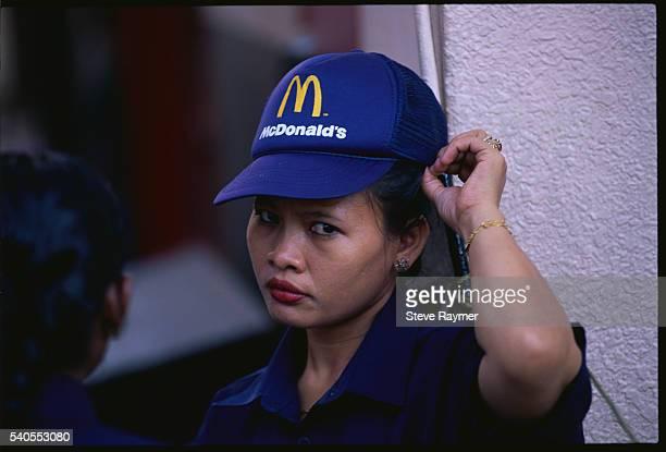 malaysian woman wearing mcdonald's hat - mcdonald's stock pictures, royalty-free photos & images
