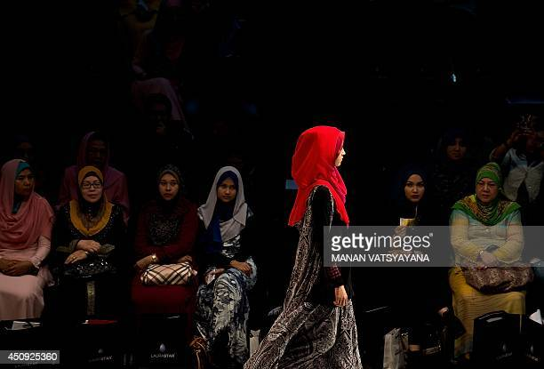 Malaysian women wearing 'hijabs' watch as a model presents creations by designer Serikapas at the Islamic Fashion Festival during 2014 Malaysia...