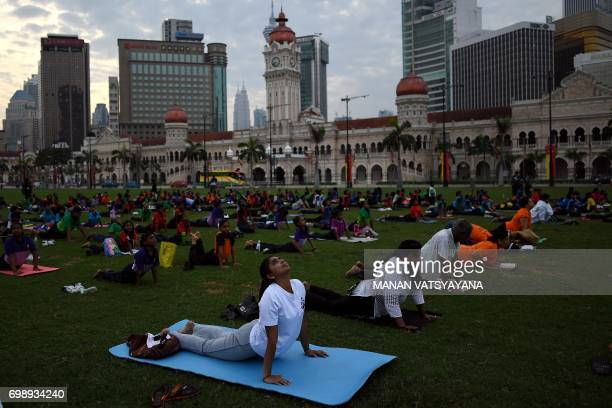 Malaysian yoga practitioners perform exercises during an event to mark International Yoga Day at the Sultan Abdul Samad building in Kuala Lumpur on...