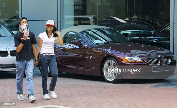 Malaysian youths walk past a luxury car showroom in Kuala Lumpur 31 December 2003 The government is expected to announce excise duties on imported...