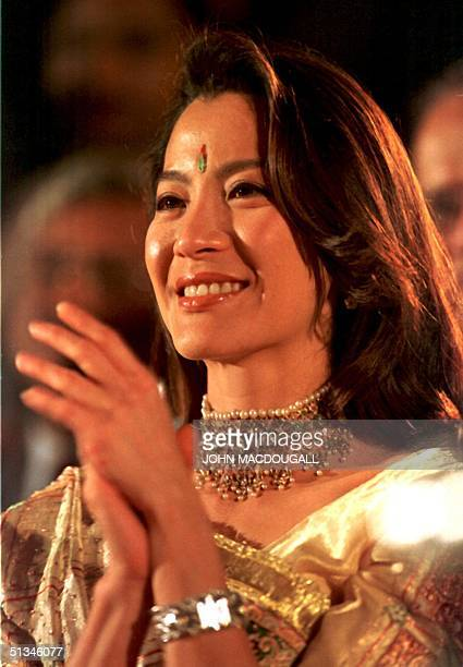 Malaysianborn actress and Bond girl Michelle Yeoh clad in traditional Indian dress applauds the contestants participating in the Mr International...