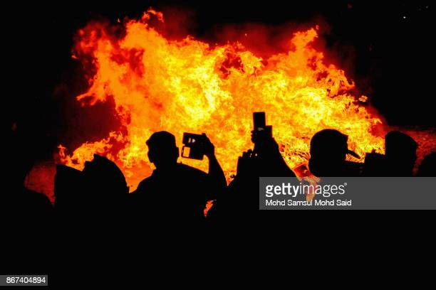 Malaysians of Chinese take a photograph of burning charcoals during the last day of Chinese Nine Emperor Gods Festival inside the temple on October...