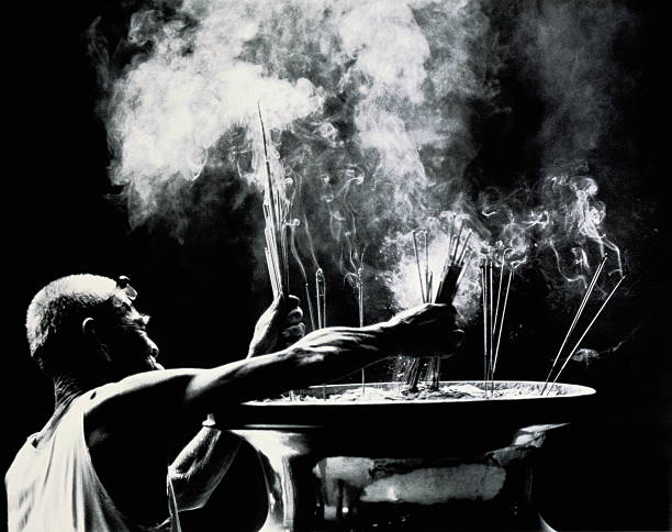 Malaysia,Penang,Georgetown,man with incense sticks at offerings bowl