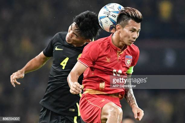 Malaysia's Adib Zainudin fights for the ball with Myanmar's Si Thu Aung during their men's football match at the 29th Southeast Asian Games at Shah...