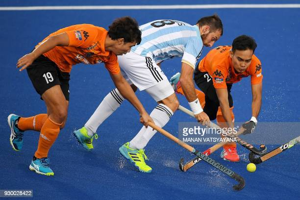 Malaysia's Azri Hassan and Azuan Hasan vie for the ball with Nahuel Salis of Argentina during their men's field hockey thirdfourth place match of the...