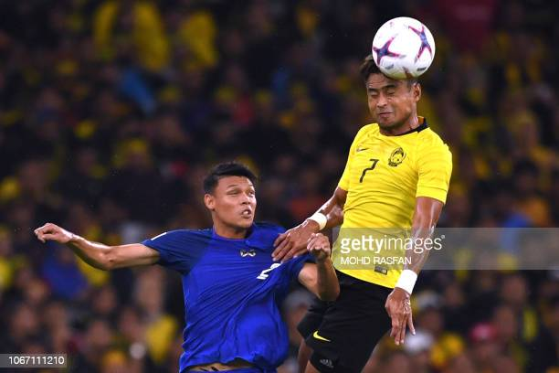 Malaysia's defender Aidil Zafuan heads the ball against Thailand's forward Supachai Jaided during the first leg of the AFF Suzuki Cup 2018 semifinal...
