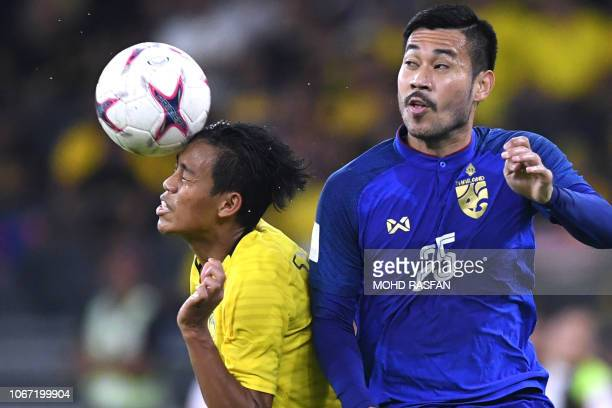 Malaysia's defender Syahmi Safari heads the ball against Thailand's midfielder Pakorn Prempak during the first leg of the AFF Suzuki Cup 2018...
