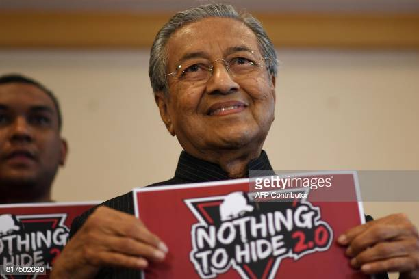 Malaysia's former prime minister Mahathir Mohamad holds a placard for the second 'Nothing To Hide' public debate following a press conference in...