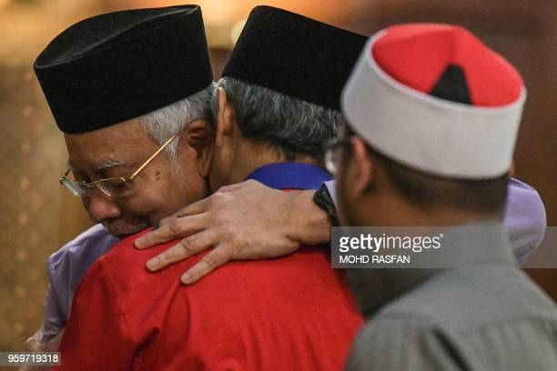 Malaysia's former prime minister Najib Razak hugs his former deputy prime minister Ahmad Zahid Hamidi before Friday prayers at the Barisan Nasional...