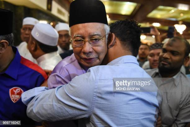 Malaysia's former prime minister Najib Razak is hugged by a supporter after Friday prayers at the Barisan Nasional party headquarters in Kuala Lumpur...
