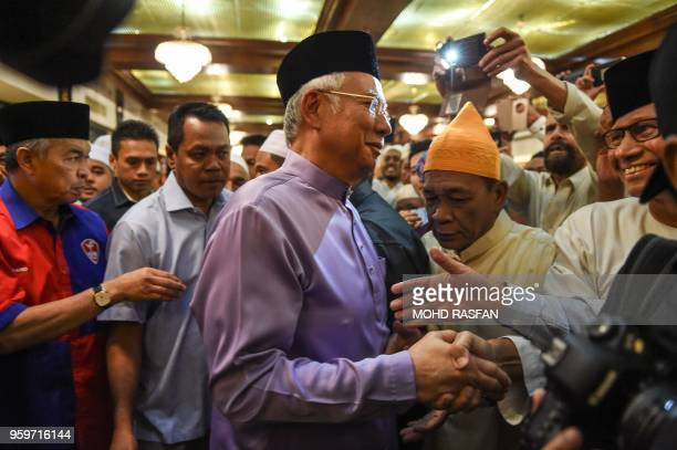 Malaysia's former prime minister Najib Razak shakes hands with supporters after Friday prayers at the Barisan Nasional party headquarters in Kuala...