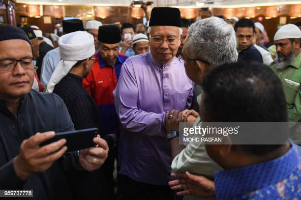 Malaysia's former prime minister Najib Razak shakes hands with Noh Omar a member of parliament for the Tanjong Karang constituency after Friday...