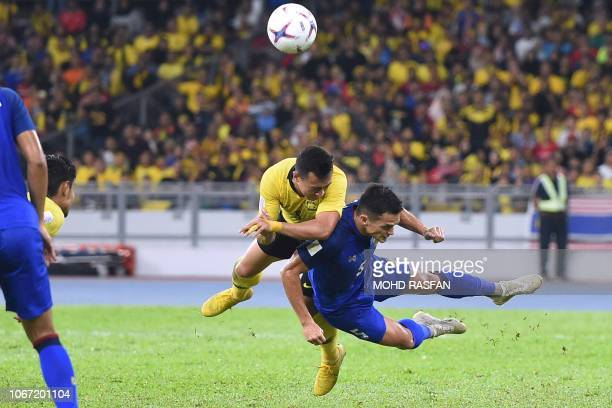 Malaysia's forward Norshahrul Idlan Talaha and Thailand's defender Mika Chunuonsee fight for the ball during the first leg of the AFF Suzuki Cup 2018...