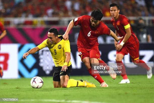 Malaysia's forward Norshahrul Idlan Talaha fights for the ball with Vietnam's midfielder Luong Xuan Truong during the 2018 AFF Suzuki Cup group A...