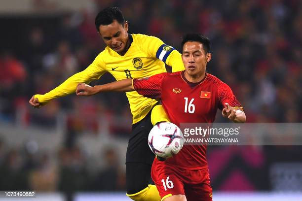 Malaysia's forward Zaquan Adha and Vietnam's midfielder Do Hung Dung fight for the ball during the AFF Suzuki Cup 2018 final football match between...