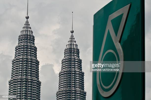 Malaysia's iconic Twin Towers are seen in the background of the Malaysian oil and gas company Petronas logo at a petrol station in Kuala Lumpur on...