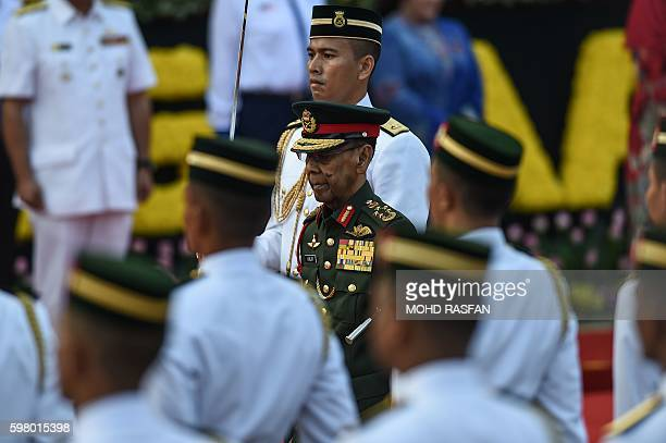 Malaysia's King Abdul Halim Mu'adzam Shah inspects a guard of honour during the 59th National Day celebrations at Independence Square in Kuala Lumpur...