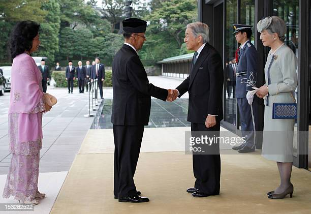 Malaysia's King Abdul Halim Mu'adzam Shah shakes hands with Japan's Emperor Akihito as Queen Haminah Hamidun and Empress Michiko look on upon their...