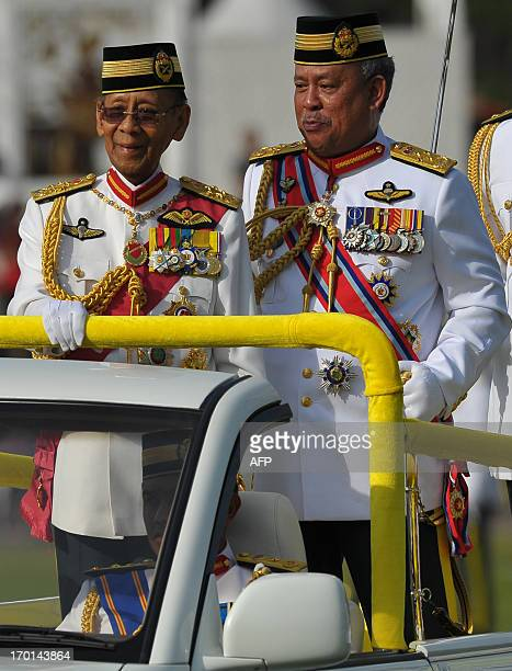 Malaysia's King Abdul Halim Mu'adzam Shah smiles as Chief of Malaysian Armed Forces Zulkifeli Mohd Zin looks on after inspecting a guard of honour...