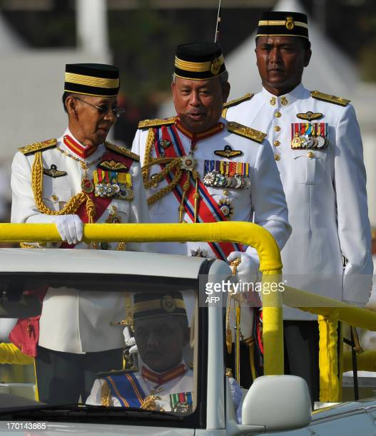 Malaysia's King Abdul Halim Mu'adzam Shah talks with Chief of Malaysian Armed Forces Zulkifeli Mohd Zin after inspecting a guard of honour during his...