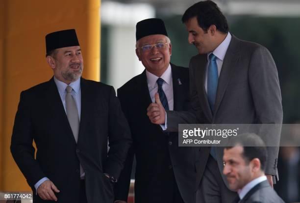 Malaysia's King Sultan Muhammad V Qatar's Emir Sheik Tamim bin Hamad alThani and Malaysia's Prime Minister Najib Razak walk together after a...