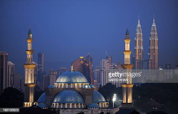 Malaysia's landmark Patronas towers stand behind a mosque in Kuala Lumpur on January 8 2010 following a day of escalating tensions in Malaysia over...