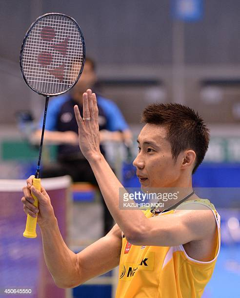 Malaysia's Lee Chong Wei acknowledges cheering fans after beating Hong Kong's Hu Yun in their men's singles final at the Japan Open badminton...