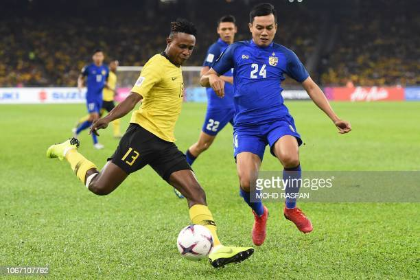 Malaysia's midfielder Mohamadou Sumareh and Thailand's defender Korrakot Wiriyaudomsiri fight for the ball during the first leg of the AFF Suzuki Cup...