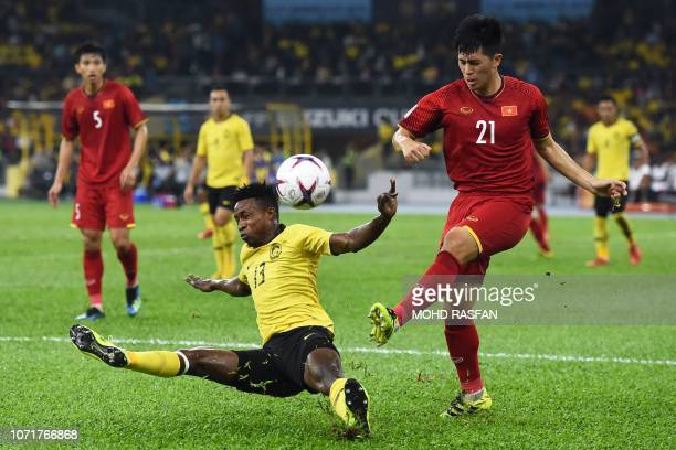 Malaysia's midfielder Mohamadou Sumareh fights for the ball with Vietnam's defender Tran Dinh Trong during the AFF Suzuki Cup 2018 final football...